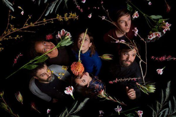 Os membros do Dirty Projectors aparecem em foto com fundo preto segurando diversas flores